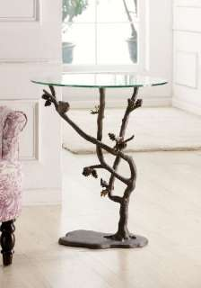 This aluminum pine cone and branch glass topped round end table makes